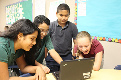 Students look at laptop as a group