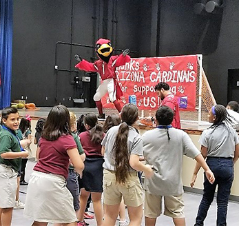 School mascot dances on stage with students in the audience
