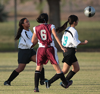 Students play soccer together on a field