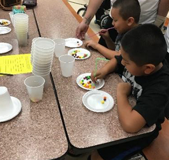 Students make crafts with candy and straws