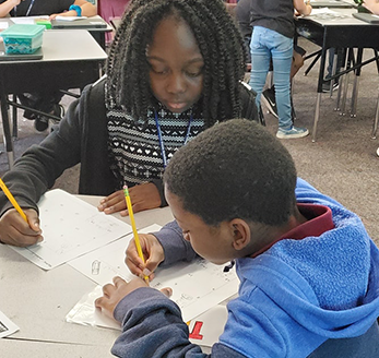 Students work together in a workbook