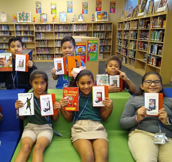 Students pose with books