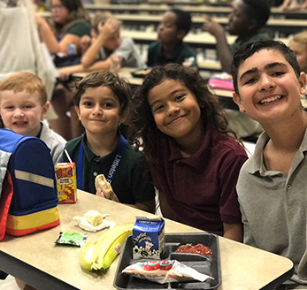 Four students pose together in the cafeteria