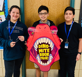 Three students pose together with a dinosaur themed dynamite book fair poster