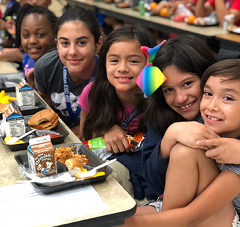 Five students pose together in the cafeteria