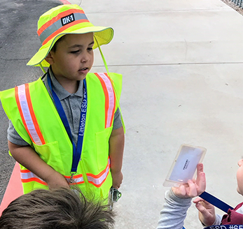 Student dressed in a neon safety vest looks at another student showing him their name tag