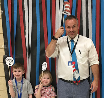Two students holding up Thing 1 and Thing 2 signs stand next to a staff member holding up a Cat in the Hat sign