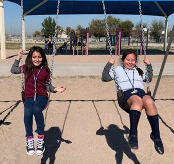 Two female students swing on swings outside