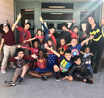 Students dressed in superhero attire pose together outside in front of a door