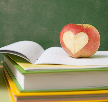 Apple with heart bite on a stack of books