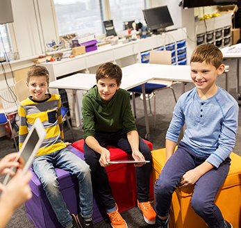 Three older elementary students smiling and listening to a fellow student