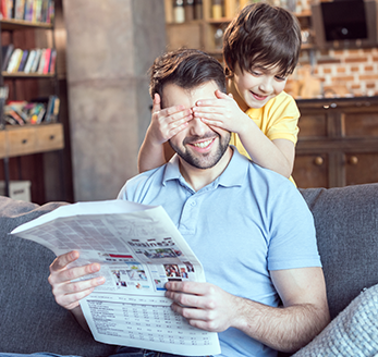 Boy covers his fathers eyes with his hands as he reads a newspaper on the couch