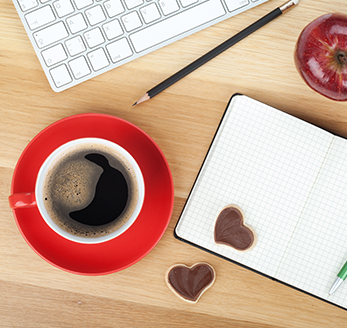 A table displaying a cup of coffee, cookies, and notebook