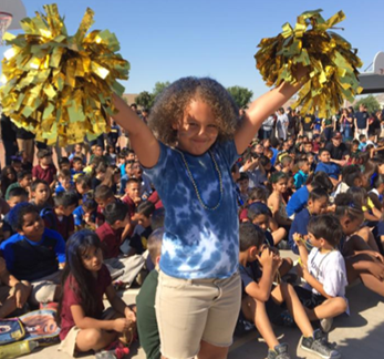 Female student holds up pom poms