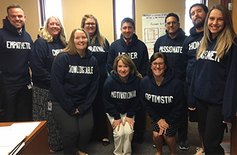 Staff members pose together wearing shirts with descriptive words on them