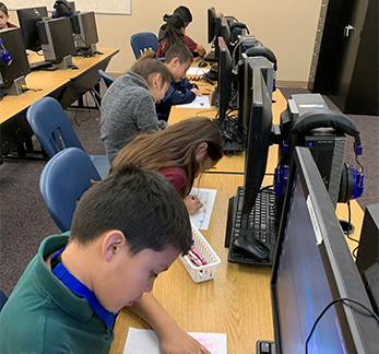 Students color on paper in front of computers