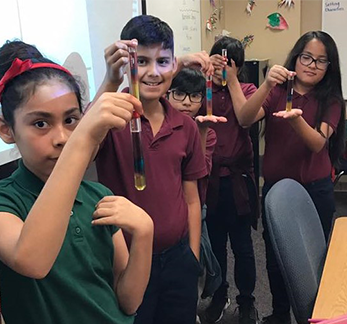 Students hold up glass vials with fluid inside