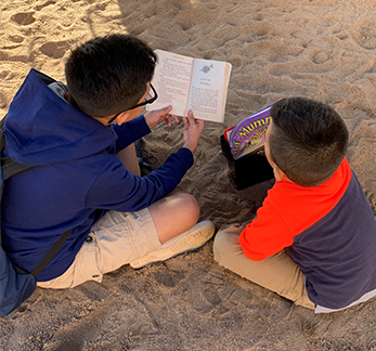 Students read together in sand