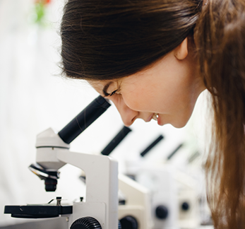 Student looks into microscope