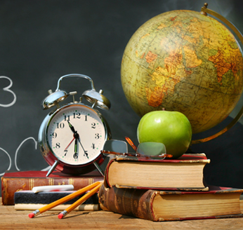 Chalkboard, clock, apple, books, pencils and a globe