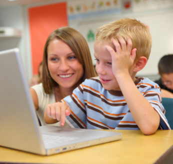 Teacher helps a student using a laptop in class