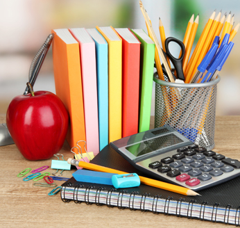 School supplies and an apple on  a table