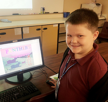 little boy standing by his computer
