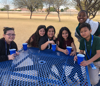 students sitting at a picnic table