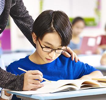 Teacher helps student with his classwork