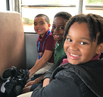 Smiling students sitting in a school bus