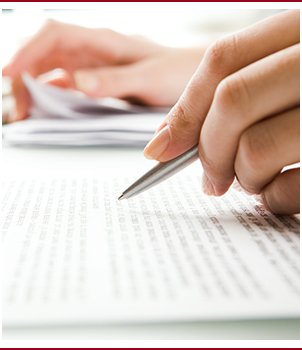 Hands hold a pen above a piece of paper