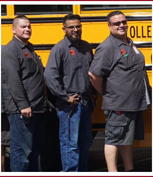 three bus drivers in front of school bus