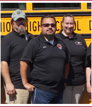 Group of transportation staff members pose together in front of a school bus