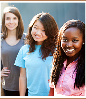 Three female students pose together outside