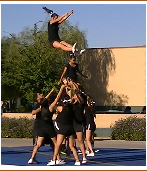 Cheerleaders catching jumping cheerleader