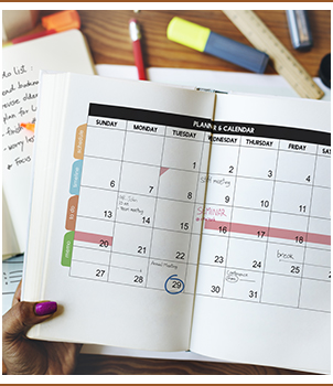 Hands holding a calendar planner open