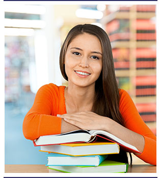 Smiling student places her arms on top of stacked books in a library