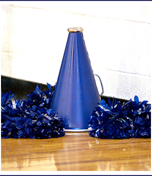 Megaphone and pom poms sit on a gym floor