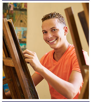 Smiling student works on an art project using an easel