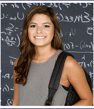 Smiling student wearing a backpack poses in front of a blackboard with equations written on it