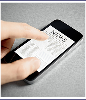 Finger touches a smartphone with a news page open