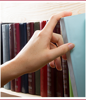 Woman's hand selecting a book from a bookshelf