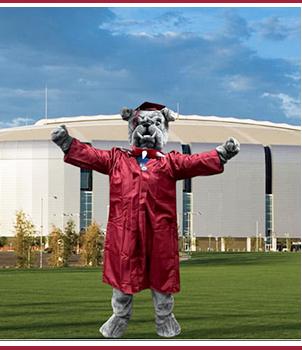 School mascot dressed in cap and gown in front of school