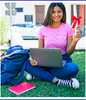 High school student sitting outside on a beautiful summer day with laptop and book