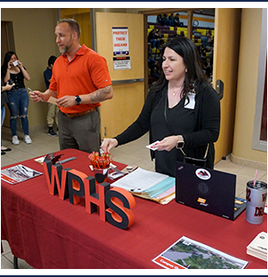 Two West Point High School representatives handing out information at a parent night session