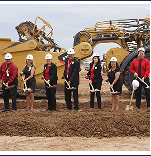Tolleson Union Leaders with posing for a picture with construction hats and shovels