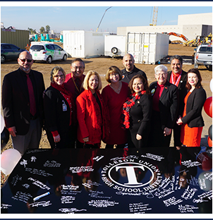 Tolleson Union leaders behind TUHSD Logo plaque with signatures outside at construction site