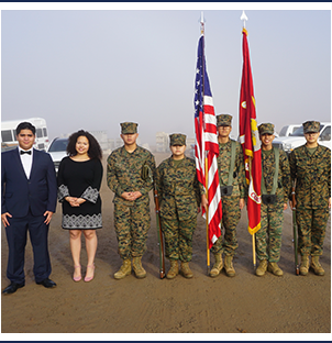 Group of JRROTC students with US and USMC flags along with two students in formal attire