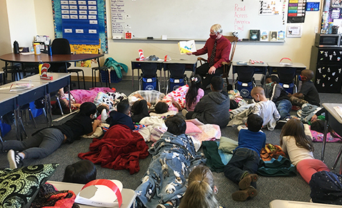 Teacher reading Dr. Seuss book to students in sleeping bags in classroom