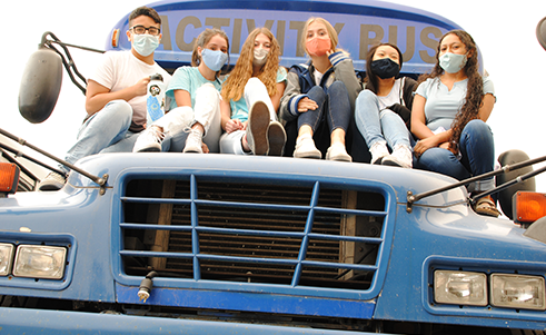 Group photo of students sitting on blue school bus